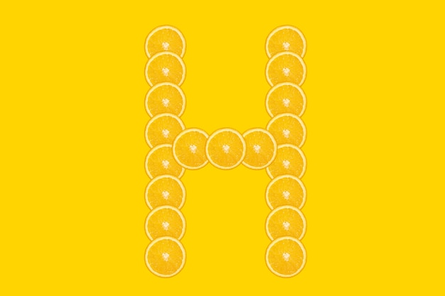 Нарезанный оранжевый алфавит - буква h. желтый фон. свежие здоровые апельсиновые плоды. сочный шрифт.