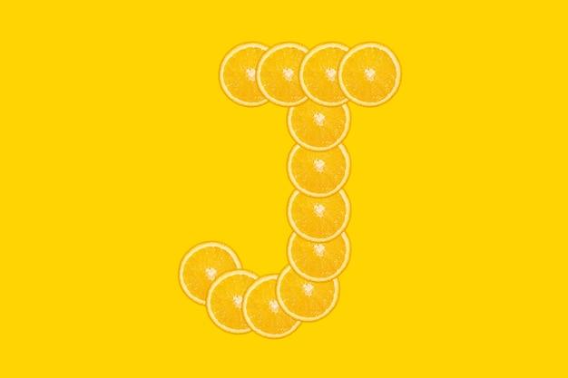 Нарезанный оранжевый алфавит - буква j. желтый фон. свежие здоровые апельсиновые плоды. сочный шрифт.