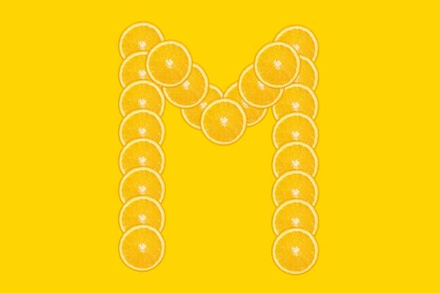 슬라이스 오렌지 알파벳-문자 m. 노란색 배경입니다. 신선한 건강 오렌지 과일입니다. 육즙이 많은 글꼴.