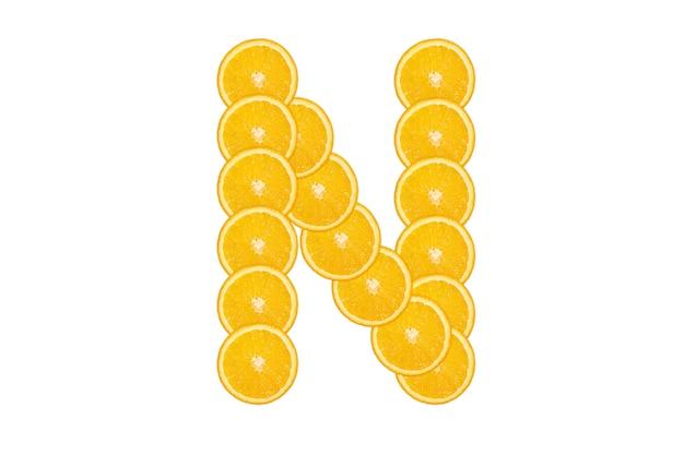 Нарезанный оранжевый алфавит - буква n. изолированный белый фон. свежие здоровые апельсиновые плоды. сочный шрифт.