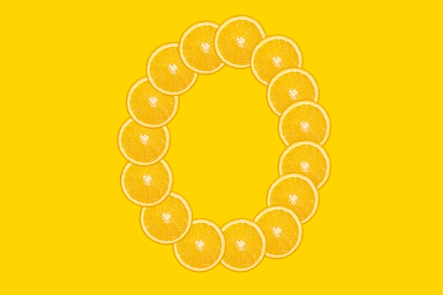 Нарезанный оранжевый алфавит - буква о. желтый фон. свежие здоровые апельсиновые плоды. сочный шрифт.