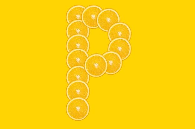 Нарезанный оранжевый алфавит - буква п. желтый фон. свежие здоровые апельсиновые плоды. сочный шрифт.