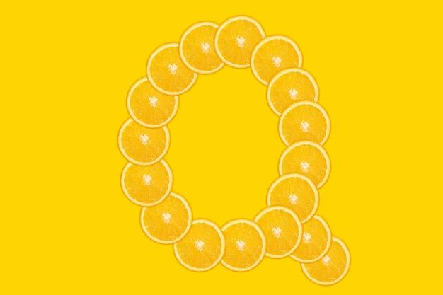 Нарезанный оранжевый алфавит - буква q. желтый фон. свежие здоровые апельсиновые плоды. сочный шрифт.