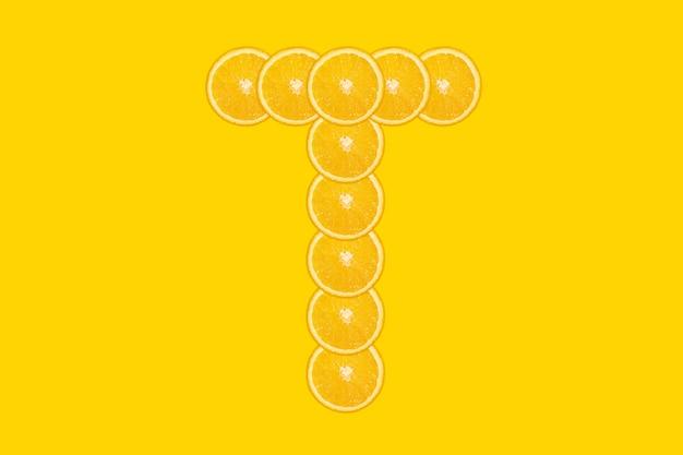 Нарезанный оранжевый алфавит - буква т. желтый фон. свежие здоровые апельсиновые плоды. сочный шрифт.