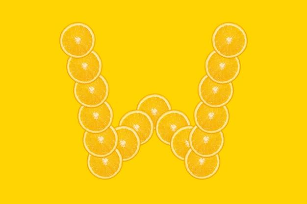 Нарезанный оранжевый алфавит - буква w. желтый фон. свежие здоровые апельсиновые плоды. сочный шрифт.