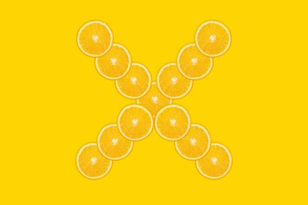 Нарезанный оранжевый алфавит - буква x. желтый фон. свежие здоровые апельсиновые плоды. сочный шрифт.