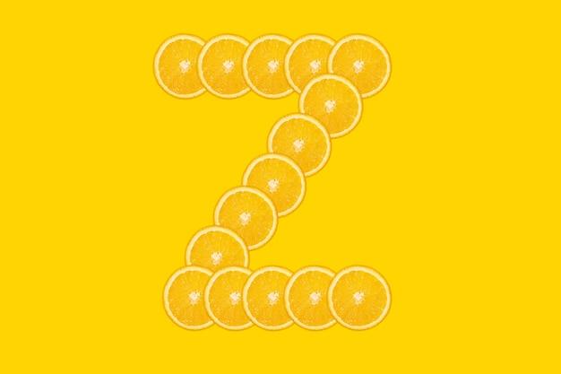 Нарезанный оранжевый алфавит - буква z. желтый фон. свежие здоровые апельсиновые плоды. сочный шрифт.