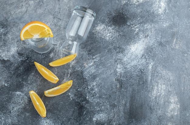 Нарезанный апельсин и пустой на мраморном столе.
