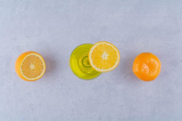 대리석 테이블에 얇게 썬 오렌지와 과일 주스.