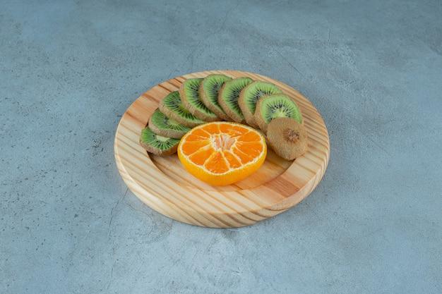 Нарезанный апельсин и киви на деревянной тарелке на мраморном фоне.