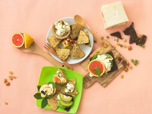 Нарезанный апельсин, авокадо, яблоко со сливочным сыром, домашнее из фруктов канапе, смешанных с хлебом, на фоне
