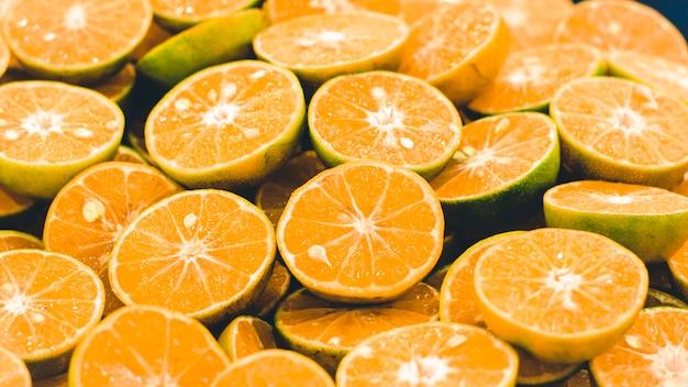 Нарезанный оранжевый фон. красочные апельсиновые кусочки цитрусовых. половина апельсина, свежий и сочный. здоровая пища и витамин с