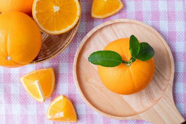 핑크 식탁보 질감 배경에 오렌지 과일을 슬라이스