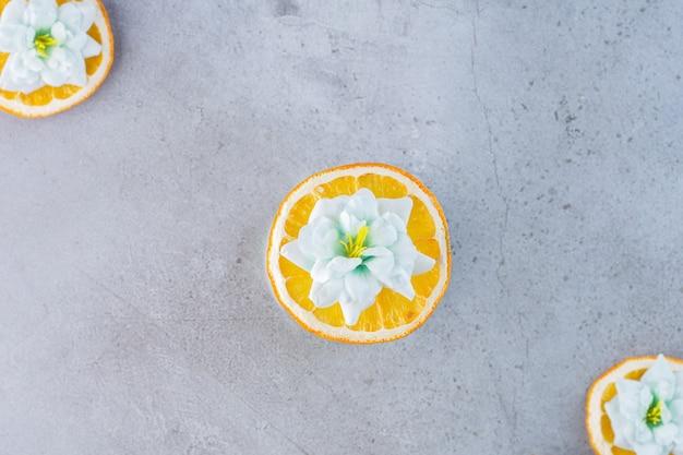 Frutta a fette di arancia con fiori bianchi su sfondo grigio