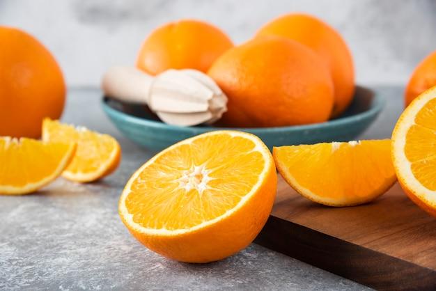Нарезанные оранжевые плоды с целыми апельсинами на деревянной доске.