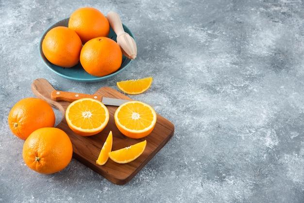 나무 보드에 전체 오렌지와 오렌지 과일 슬라이스.