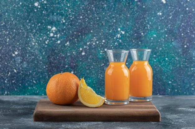 Sliced orange and juice on wooden board.