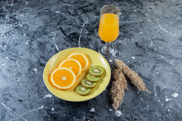 Sliced orange and kiwi on yellow plate with glass of juice.