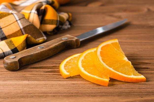 Sliced orange, knife and napkin on a wooden table
