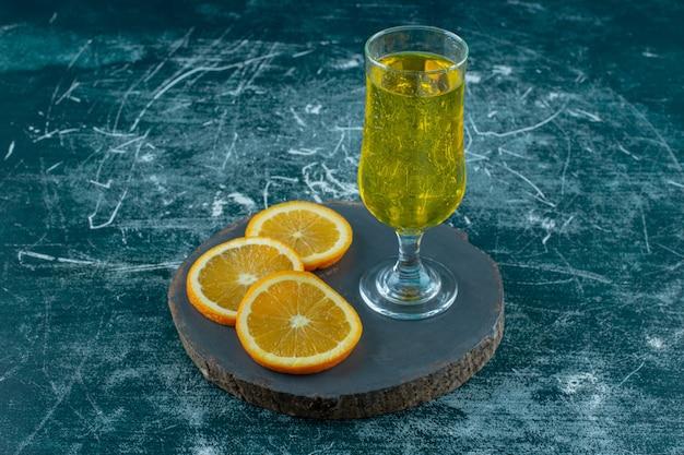 Нарезанный апельсин рядом с грушевым соком на доске, на синем фоне.