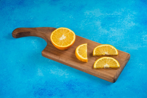 Нарезанный апельсин на деревянной доске на синем.
