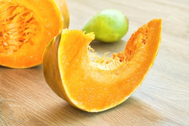 Нарезанная апельсиновая спелая тыква с ломтиком на деревянном столе