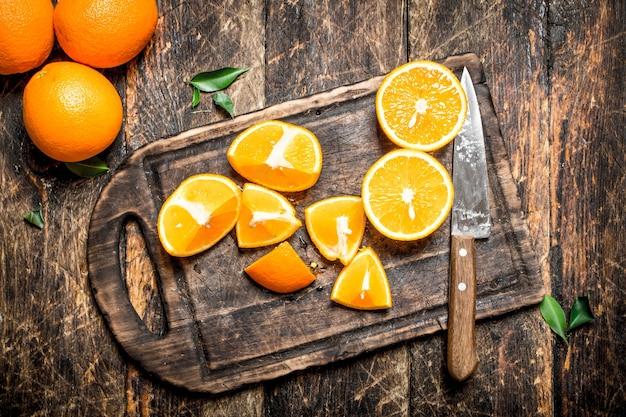 まな板の上でオレンジスライスをナイフでスライスしました。木製の背景に。