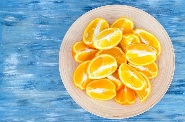 Sliced orange slices on wooden plate.