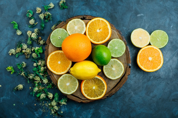 Sliced orange with lime, lemon, dried flowers flat lay on grungy blue and wooden board