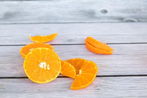 과일 광고를 위해 만든 나무가 우거진 접시에 얇게 썬 오렌지를 놓습니다.