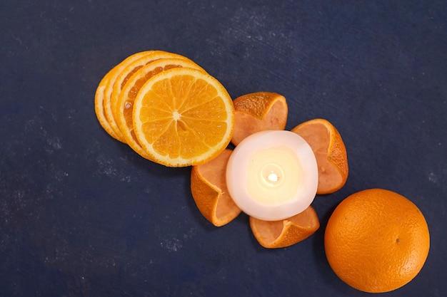 Нарезанные апельсины в кучу на синем фоне, вид сверху. фото высокого качества