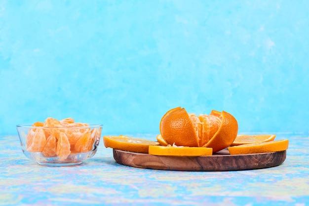 Fette di arance e mandarini isolati su un piatto di legno e in una tazza di vetro su sfondo blu. foto di alta qualità