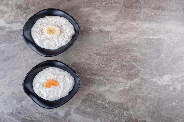 Нарезанные апельсины на миске с кашей рядом с нарезанным бананом на миске с кашей на мраморном фоне.