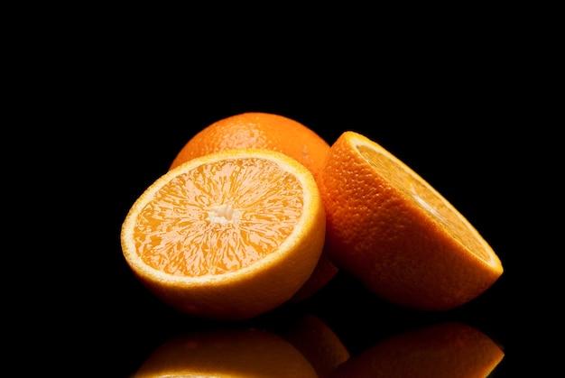 Нарезанные апельсины на черном фоне. студийный снимок