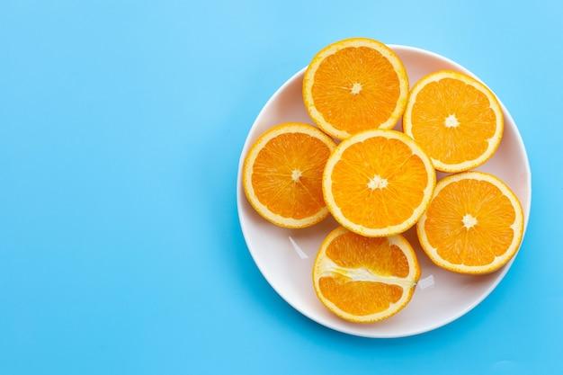 Нарезанные апельсины на синем. высокое содержание витамина с, сочное и сладкое.
