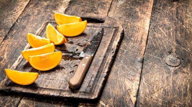 木製の背景のまな板にスライスしたオレンジ