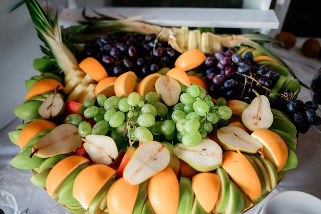 Sliced oranges, pears, apples and grape served on large dish