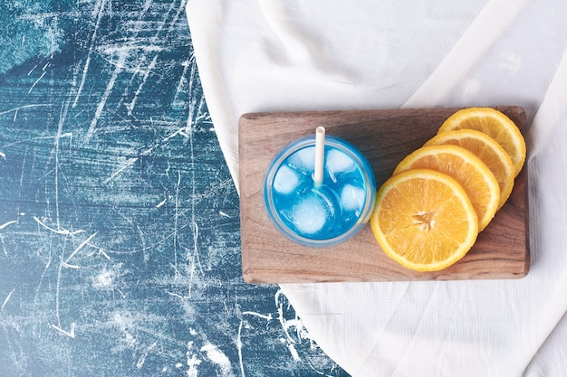 Sliced oranges with a glass of juice on blue.