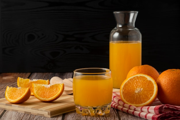Sliced oranges with juice in the glass jar and cup