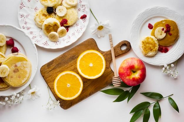 Нарезанные апельсины с блинами и фруктами