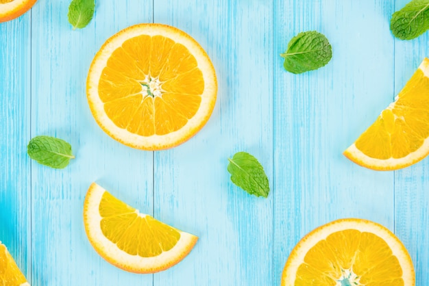 Sliced oranges with pepperment leaves on pastel light blue wood background