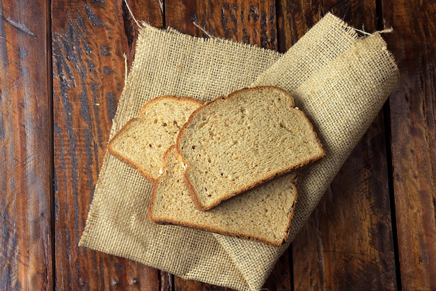 Sliced organic wholemeal bread on rustic fabric