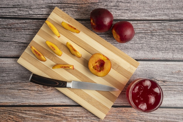 Sliced peach on a wooden cutting board with a cup of ice drink