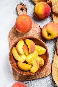 スライスした桃、木製のボウルに有機フルーツ