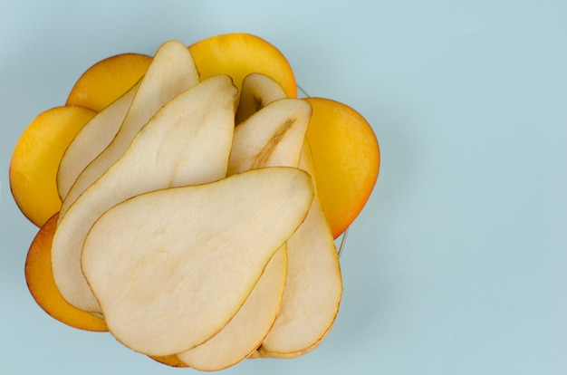 Sliced pear and nectarine on pastel blue background