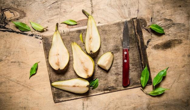 古いまな板の上でスライスした梨と木製のテーブルの葉。上面図