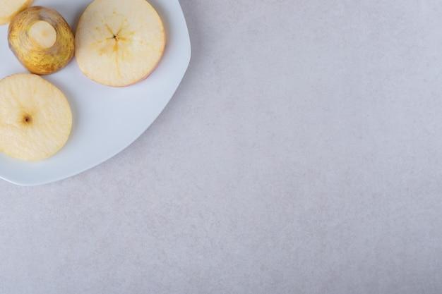 Pere affettate su un piatto sulla tavola di marmo.