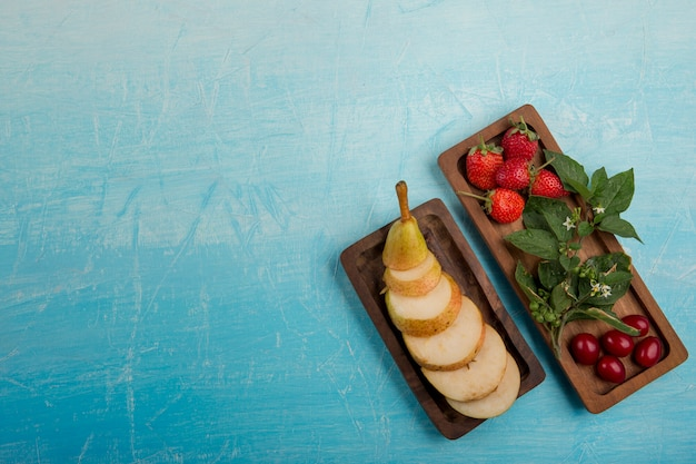 Sliced pears with strawberries and mulberries in wooden platters in the right side