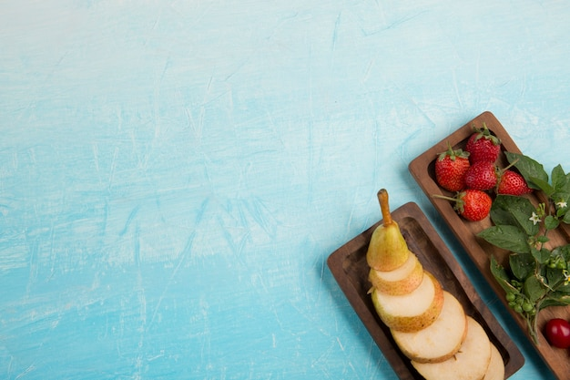 Sliced pears with strawberries and other berries in wooden platters in the corner