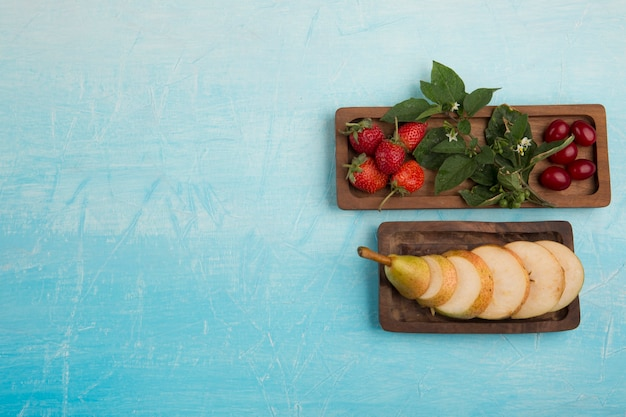Sliced pears with strawberries and other berries in wooden platters
